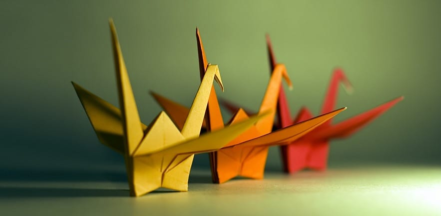 A group of 3 origami birds with the focus on the beak of the yellow bird.