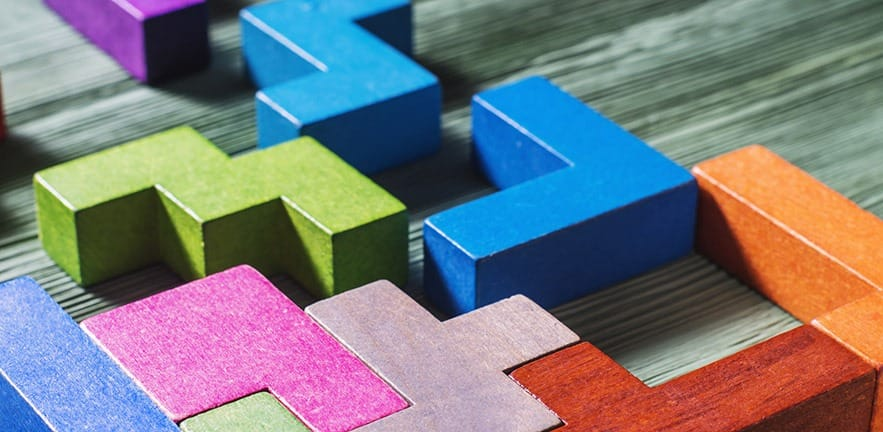 The concept of logical thinking. Geometric shapes on a wooden background. Tetris toy wooden blocks.