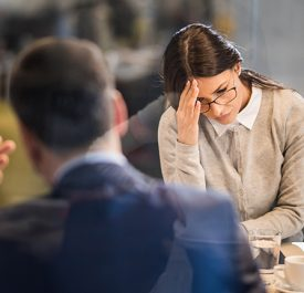 Woman in a work meeting feeling disappointed after failing at work.
